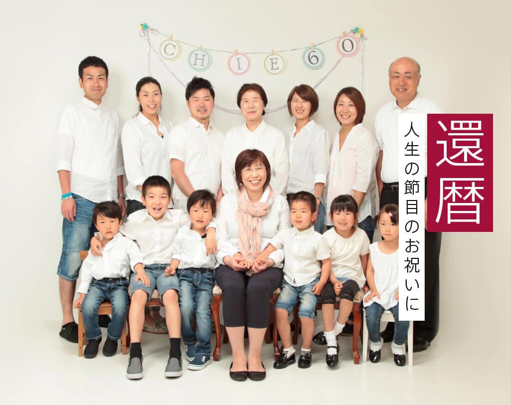 女性の還暦祝いに写真を撮る家族