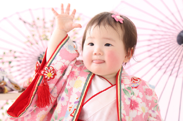 桃の節句の衣装を着て手を上げる赤ちゃん